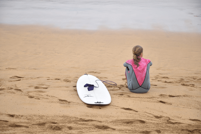 Girl looking towards ocean by a surfboard.